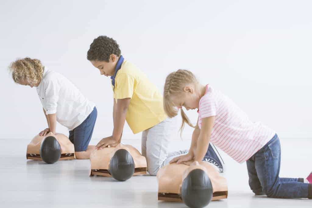 Kids doing resuscitation training on medical dummy during first aid course