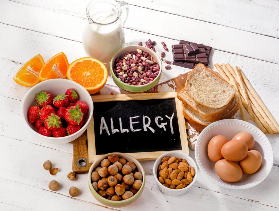 Food allergy. Allergic food on wooden background.